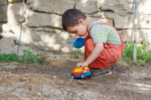 little boy plays in a puddle with the car